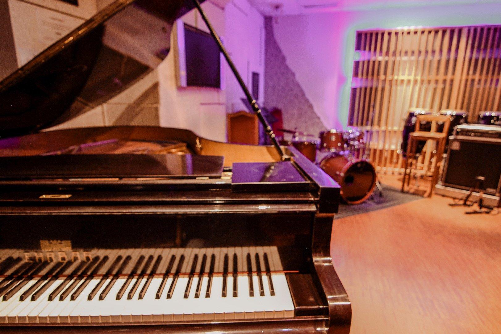 Bild unseres Raum 6 mit Ehrbar-Flügel, Yamaha Custom Drums und Ampeg Bass-Stack im Hintergrund